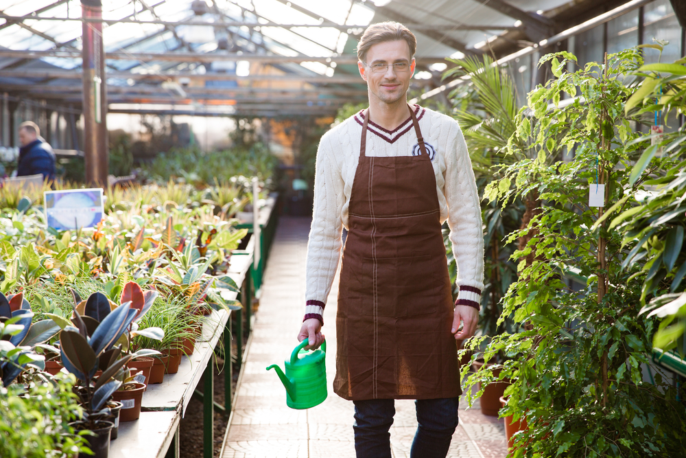 Smiling man gardener in glasses and brown apron standing and holding watering can in orangery